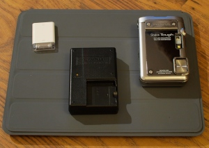 Olympus Toughie 8010 with charger and iPad SD card reader sitting on iPad