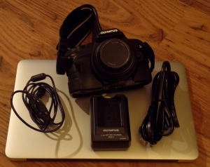 Olympus e420 with cables and charger sitting on Mac Air